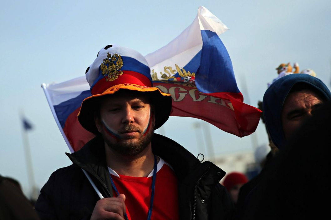 A fan holding a Russian flag in Olympic Park reacts during Russia's 3-1 loss to Finland in men's ice hockey at the Winter Olympics in Sochi, Russia, Wednesday, Feb. 19, 2014. (Brian Cassella/Chicago Tribune/MCT)