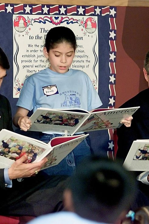 "HOUSTON, UNITED STATES:  US President George W. Bush (R) and Texas Governor Rick Perry (L) listen while schoolgirl Nancy Jara (C) reads from US second lady Lynne Cheney's new children's book ""America: A Patriotic Primer"" during a visit to the association for the Advancement of Mexican Americans 14 June, 2002 in Houston, Texas. President Bush spent 20 minutes touring the facility with the governor of Texas before participating in an evening fund raiser for his former Lt. Governor.   AFP PHOTO/TIM SLOAN (Photo credit should read TIM SLOAN/AFP/Getty Images)"