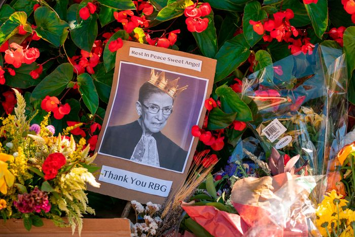 A photograph of Ruth Bader Ginsburg surrounded by flowers at a memorial to her. New York Governor Cuomo has called for an RBG statue memorial in Brooklyn.