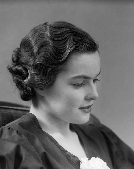 "Developed by coiffeur Francois Marcel Grateau in 1872, the ""<i>ondulation</i> Marcel"" replicated the look of labor-intensive finger waves with reverse-curling tongs. Marcel's deeply set corrugated curls defined Hollywood glamour in the twenties and thirties, before being displaced by the permanent wave."