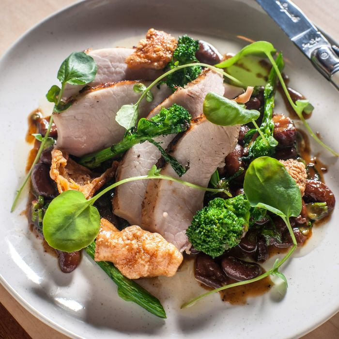 Heritage milk-fed pig: slow-roasted leg with bean ragout and broccoli rabe.