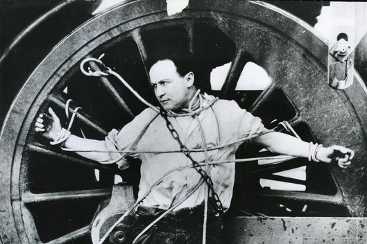 In a publicity stunt Harry Houdini chains himself to a locomotive wheel for an escape attempt around 1910.