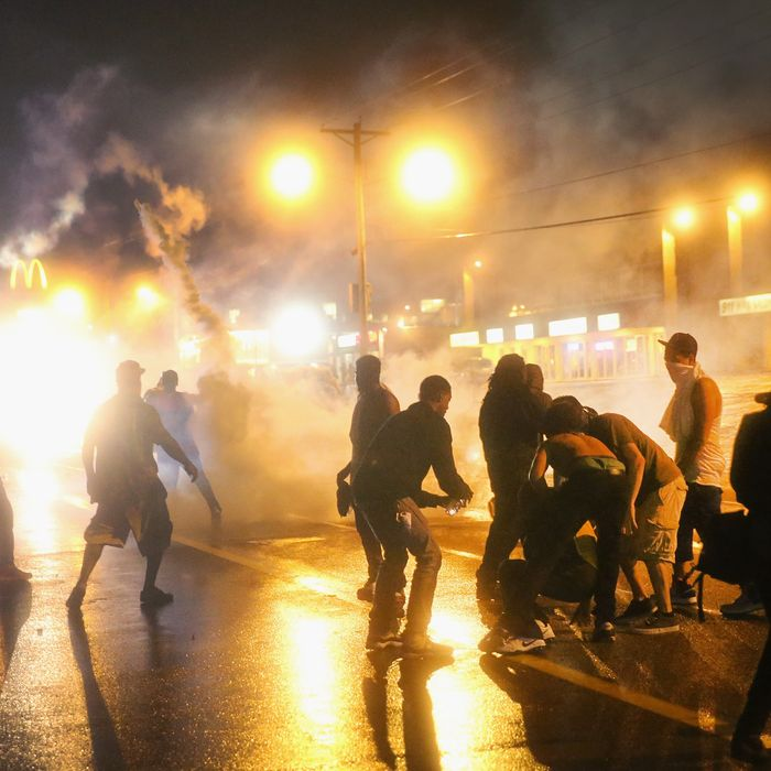 FERGUSON, MO - AUGUST 17: Police fire tear gas at demonstrators protesting the shooting of Michael Brown after they refused to honor the midnight curfew on August 17, 2014 in Ferguson, Missouri. The curfew was imposed on Saturday in an attempt to reign in the violence that has erupted nearly every night in the suburban St. Louis town since the shooting death of teenager Michael Brown by a Ferguson police officer on August 9. (Photo by Scott Olson/Getty Images)