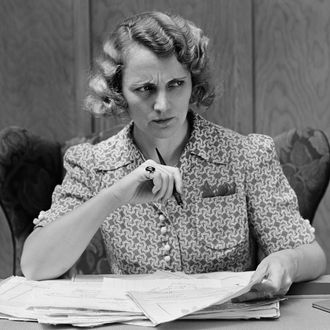 Serious worried woman at desk going over papers bills looking off to side.