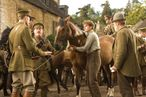 """WAR HORSE""  DM AC 33426R  Captain Nicholls (Tom Hiddleston, far left) and Sergeant Perkins (Geoff Bell) prepare to take Joey away with them. Albert (Jeremy Irvine, center) holds on to Joey defiantly while his father (Peter Mullan, right) looks on in this scene from DreamWorks Pictures' ""War Horse"". Director Steven Spielberg's epic adventure is set against a sweeping canvas of rural England and Europe during the First World War.  Ph: Andrew Cooper, SMPSP  ©DreamWorks II Distribution Co., LLC.  All Rights Reserved."