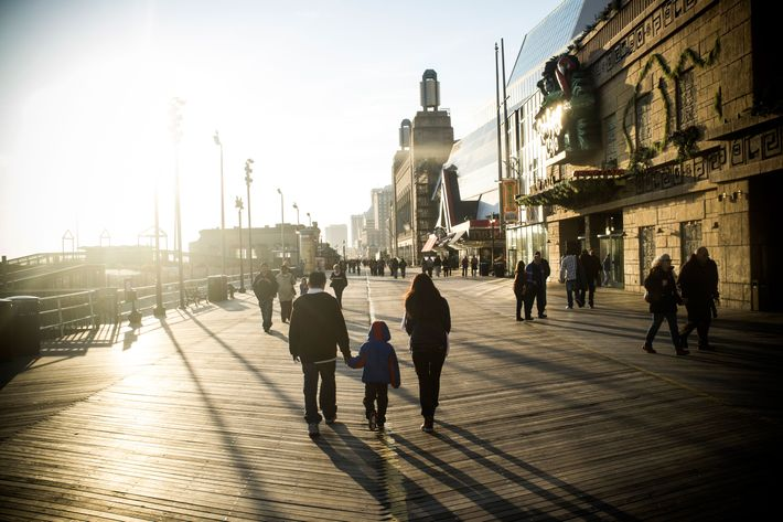 Tourists and residents walk along the crowded boardwalk on December 1, 2012 in Atlantic City, NJ.