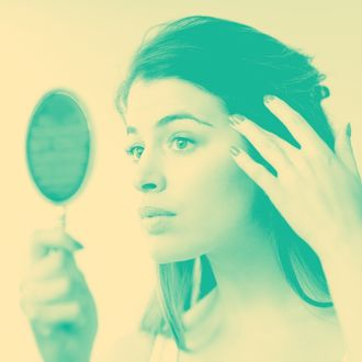 Young woman looking in hand mirror