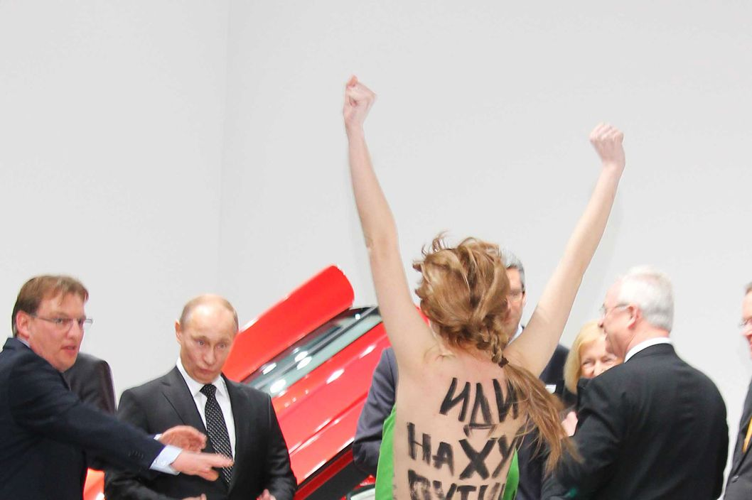 Bare-breasted woman protest against Vladimir Putin at a trade fair in Germany. The anti-Putin activist seem to be part of feminist group Femen