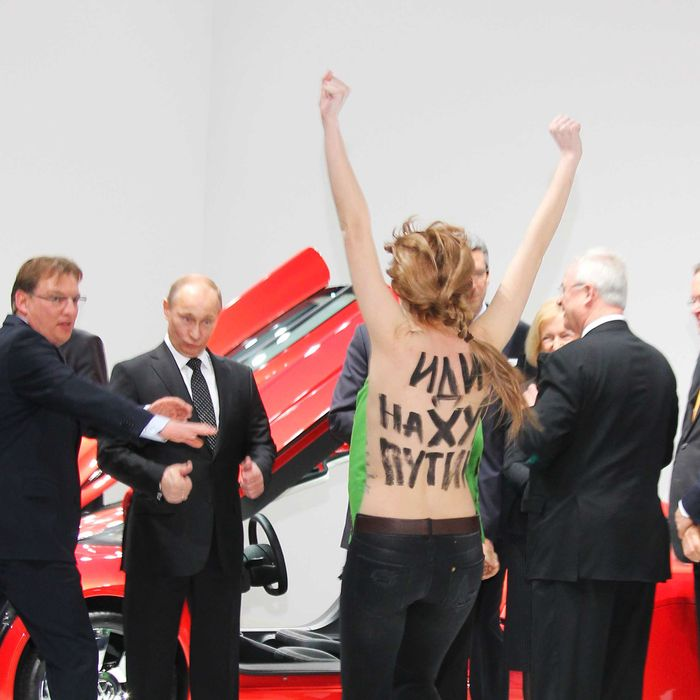 Bare-breasted woman protest against Vladimir Putin at a trade fair in Germany. The anti-Putin activist seem to be part of feminist group Femen.