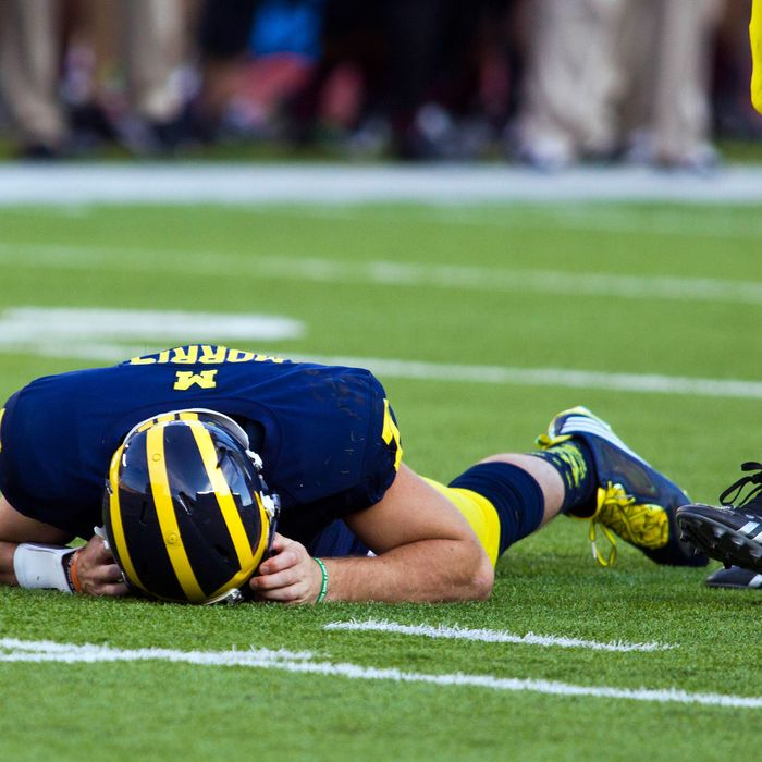 In this Sept. 27, 2014, photo, Michigan quarterback Shane Morris lays on the field after taking a hit in the fourth quarter of an NCAA college football game against Michigan in Ann Arbor, Mich. Early Tuesday, Sept. 30, 2014, roughly 12 hours after embattled Michigan coach Brady Hoke said he'd been given no indication that Morris had been diagnosed with a concussion, athletic director Dave Brandon revealed in a post-midnight statement that the sophomore did appear to have sustained one.