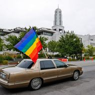 A car flies the gay pride flag in protest past the Mormon Conference center during the Semi-Annual General Conference of the Mormon church