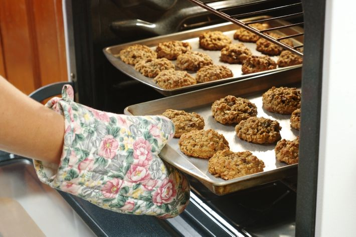 Detail of a cook's hand pulling out baked oatmeal-raisin cookies from an oven.