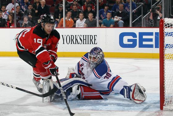 NEWARK, NJ - DECEMBER 20: Travis Zajac #19 of the New Jersey Devils tries the control the puck in front of Henrik Lundqvist #30 of the New York Rangers at the Prudential Center on December 20, 2011 in Newark, New Jersey.  (Photo by Bruce Bennett/Getty Images)