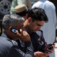 Pakistani policemen use their mobile phones at a street in Quetta on May 20, 2010. AFP PHOTO/BANARAS KHAN (Photo credit should read BANARAS KHAN/AFP/Getty Images)