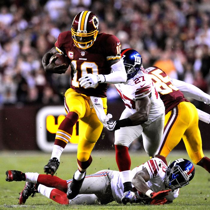 Quarterback Robert Griffin III #10 of the Washington Redskins runs the ball between Stevie Brown #27 and Prince Amukamara #20 of the New York Giants in the third quarter at FedExField on December 3, 2012 in Landover, Maryland.