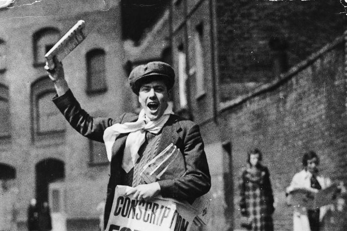 1939: A newspaper boy with a poster calling for the conscription of all 20-year-old men during World War II. (Photo by Keystone/Getty Images)