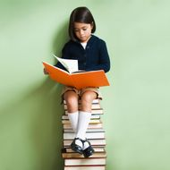 Mixed race girl sitting on stack of books reading book --- Image by ? KidStock/Blend Images/Corbis