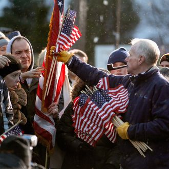 WEST DES MOINES, IA - DECEMBER 30: As a light and steady rain falls, Jim Wilson of Buckingham, Virginia, hand out United States flags to supporters before the start of a campaign rally with former Massachusetts Governor and Republican presidential candidate Mitt Romney at a Hy Vee supermarket December 30, 2011 in West Des Moines, Iowa. Despite cold wind and rain, hundreds of Romney supporters came out to see the candidate just days before the