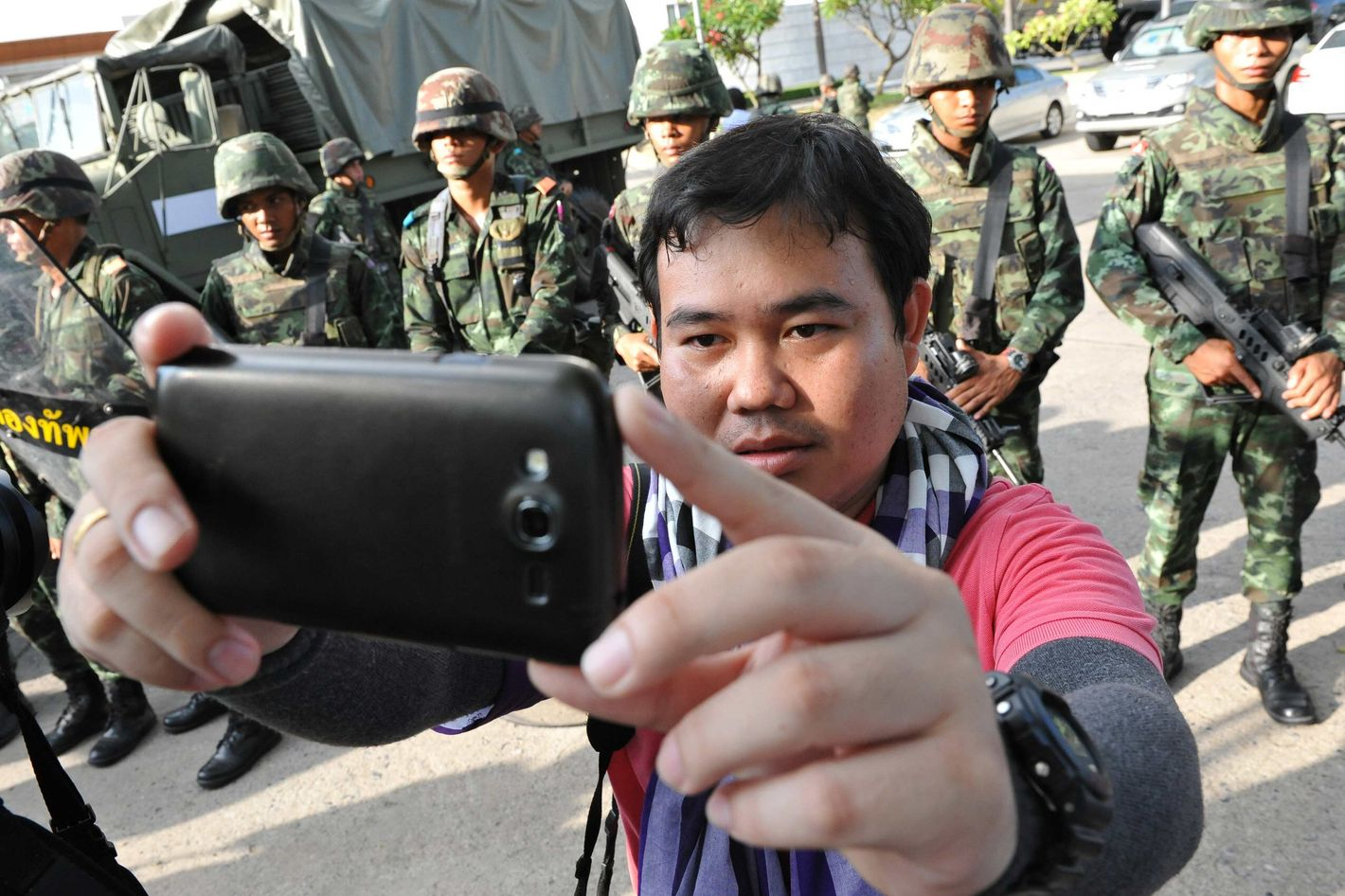 """A member of the press takes a """"selfie"""" with Thai army soldiers standing guard at the grounds of the venue for peace talks between pro- and anti-government groups on May 22, 2014 in Bangkok, Thailand. The army chief announced in an address to the nation that the armed forces were seizing power amid reports that leaders of the opposing groups attending the talks were being detained by the military. Thailand has seen months of political unrest and violence which has claimed at least 28 lives."""