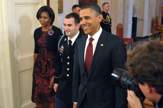 US President Barack Obama (R) and First Lady Michelle Obama walk into the East Room with Staff Sergeant Salvatore Giunta of the US Army (C) for a Medal of Honor presentation ceremony for Giunta November 16, 2010 at the White House in Washington, DC. Giunta is the first living recipient of the Medal of Honor since the Vietnam War. AFP PHOTO/Mandel NGAN (Photo credit should read MANDEL NGAN/AFP/Getty Images)