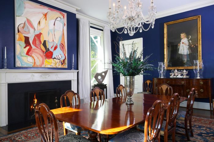 A dining room furnished with a Regency-style table, console, and chairs; Persian rug, abstract artwork; and