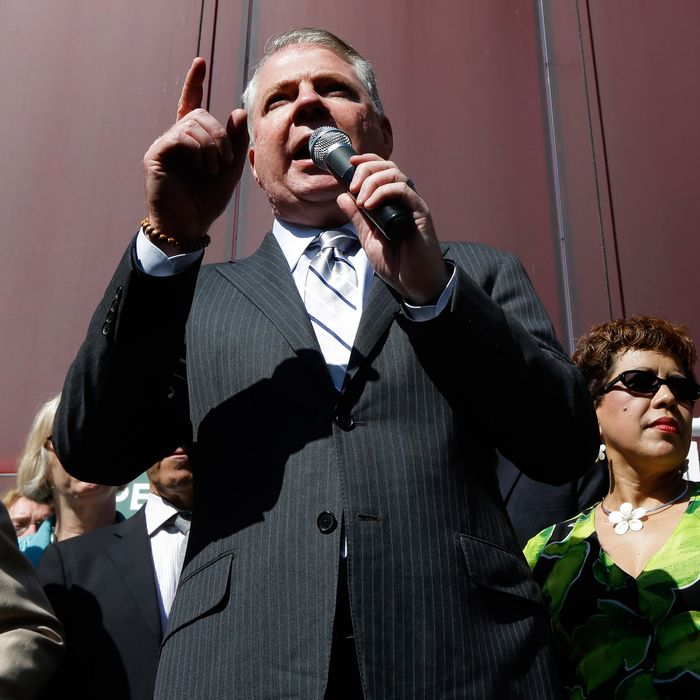 Seattle Mayor Ed Murray, left, stands with supporters of Seattle's $15 minimum wage law as he speaks Monday, June 2, 2014, at a rally outside Seattle City Hall after the Seattle City Council passed the $15 minimum wage measure in a meeting.