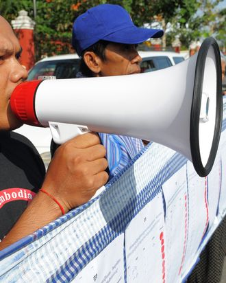 A Cambodian man shouts slogans as people hold a 230-meters long petition during a protest in front of the National Assembly building in Phnom Penh on December 20, 2011. Cambodian people and rights activists filed a petition at the National Assembly to request the body not to adopt a controversial draft of the law on Associations and NGOs. They said the law is being created with an intention to control rather than to promote and strengthen civil society, and as such it undermines the rights of the people and shrinks democratic space in Cambodia.