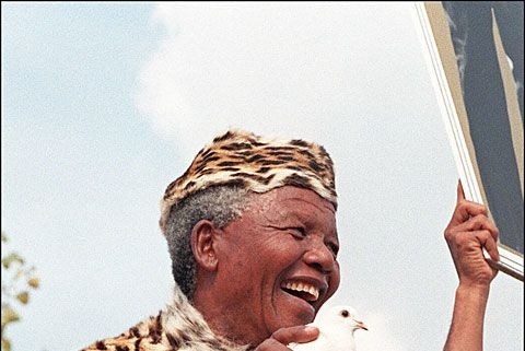 ANC President Nelson Mandela clothed in leopard skin traditional clothes releases a white dove for peace at a rally to commemorate the 34th anniversary of the massacre of 69 black demonstrators by the police in Sharpville, south of Johannesburg.