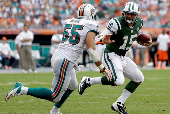 New York Jets quarterback Tim Tebow (15) carries the ball as Miami Dolphins outside linebacker Koa Misi (55) pursues during the second half of an NFL football game, Sunday, Sept. 23, 2012, in Miami. (AP Photo/Lynne Sladky)