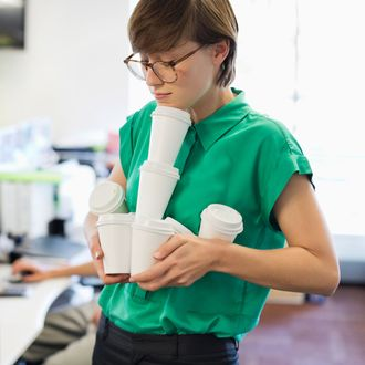 Businesswoman balancing empty coffee cups