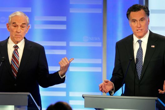 Rep. Ron Paul, R-Texas, points to former Massachusetts Gov. Mitt Romney as he answers a question during a Republican presidential candidate debate at Saint Anselm College in Manchester, N.H., Saturday, Jan. 7, 2012. (AP Photo/Elise Amendola)