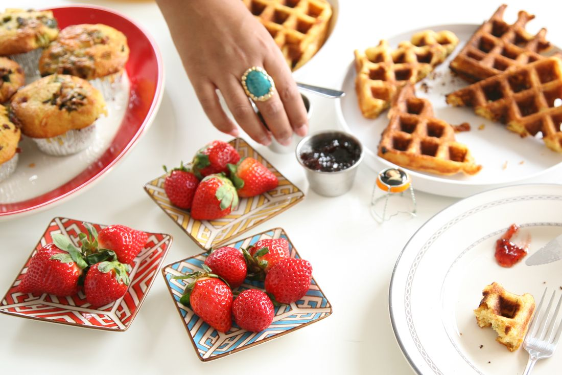 A tablescape filled with half-eaten breakfast dishes, like muffins, waffles, and strawberries.