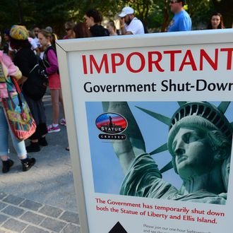 Tourists walk by a sign announcing that the Statue of Liberty is closed due to a US government shutdown in New York, October 1, 2013. Government institutions and national parks around the US were closed and thousands of employees were furloughed after Congress was unable to agree on a federal budget and shut down the goverment for the first time in 17 years.