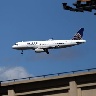 NEW YORK, NY - APRIL 05: A United Airlines airplane flies along it's landing path towards LaGuardia International Airport as the New York Mets host the Atlanta Braves during their Opening Day Game at Citi Field on April 5, 2012 in New York City. (Photo by Nick Laham/Getty Images)