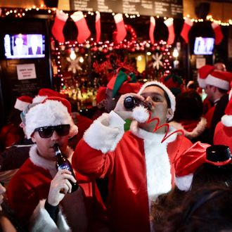 NEW YORK, NY - DECEMBER 14: Revelers dressed as Santa Claus drink inside at a bar in the East Village neighborhood during the annual SantaCon bar crawl event on December 14, 2013 in New York City. The SantaCon annual event occurs worldwide in more than 300 cities in 44 countries. In New York some community groups have established a 'Santa Free' zone that urges bars not to serve alcoholic beverages to people participating in order to dissuade incidents of public vomiting and urination in the streets. (Photo by Kena Betancur/Getty Images)