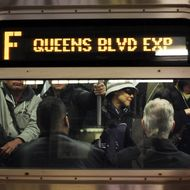 Commuters ride the F train