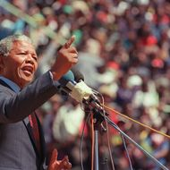 Anti-apartheid leader and African National Congress (ANC) member Nelson Mandela addresses at a funeral of 12 people died during recent township unrests in Soweto, 20 September 1990, in Soweto. (Photo credit should read ALEXANDER JOE/AFP/Getty Images)