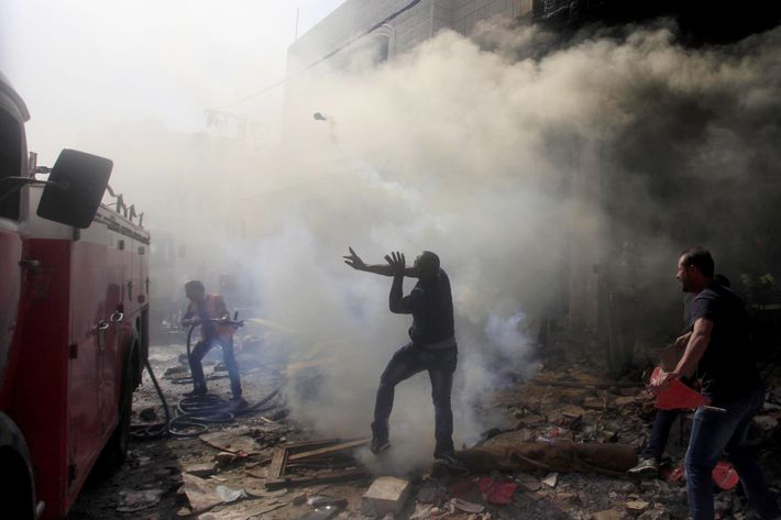 A Palestinian demonstrator throw a teargas canister back to Isreali soldiers in Hebron, also known as al-Khalil, West Bank, on September 23, 2014. Following the killings of two Palestinians accused of kidnapping and killing three Jewish settlers in the West Bank city of Hebron and Police raids in some areas of the city, a brawl took place  between Palestinians and Israeli soldiers. Israeli soldiers used real and rubber bullets besides teargas.