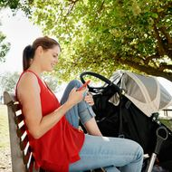 Young mother resting in the shade of the trees on a park bench, texting.Location Gold Coast, Queensland, Australia. --- Image by ? Michael Pole/Corbis