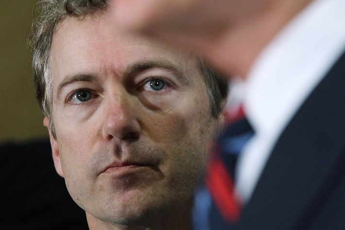 DES MOINES, IA - JANUARY 02: U.S. Sen. Rand Paul (R-KY) (L) looks on as his father, Republican presidential hopeful U.S. Rep Ron Paul (R-TX) speaks during a campaign stop at the Downtown Des Moines Marriott Hotel on January 2, 2012 in Des Moines, Iowa. With one day to go before the Iowa caucuses, Ron Paul makes a final campaign push with a whistle-stop tour through Iowa. (Photo by Justin Sullivan/Getty Images)