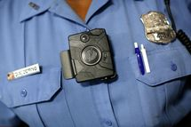 """WASHINGTON, DC - SEPTEMBER 24:  Washington DC Metropolitan Police Officer Debra Domino wears one of the new """"body-worn cameras"""" that the city's officers will begin using during a press conference announcing the details of the program September 24, 2014 in Washington, DC. The MPD's use of the cameras is intended to accurately document events, actions, conditions, and statements made during citizen encounters, traffic stops, arrests, and other incidents with the city's police officers.  (Photo by Win McNamee/Getty Images)"""