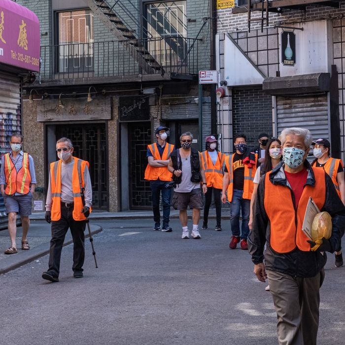 A group of Asian and white people in orange vests walk down a street with shuttered storefronts.