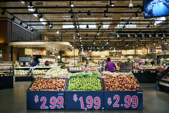A grocery display with three kinds of apples in the produce section of Wegmans supermarket