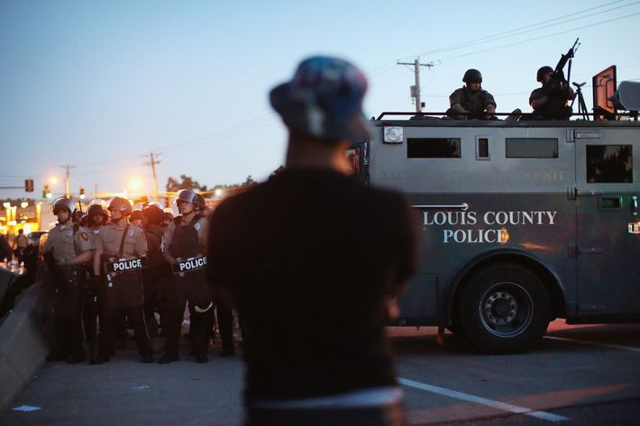 FERGUSON, MO - AUGUST 13:  Police stand watch as demonstrators protest the shooting death of teenager Michael Brown on August 13, 2014 in Ferguson, Missouri. Brown was shot and killed by a Ferguson police officer on Saturday. Ferguson, a St. Louis suburb, is experiencing its fourth day of violent protests since the killing.  (Photo by Scott Olson/Getty Images)