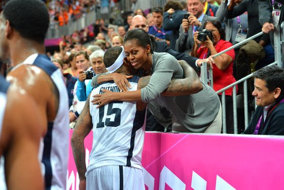 LONDON, ENGLAND - JULY 29: Carmelo Anthony #15 of the USA Mens Senior National team hugs The First Lady Michelle Obama after defeating France 98-71 at the Olympic Park Basketball Arena during the London Olympic Games on July 29, 2012 in London, England. NOTE TO USER: User expressly acknowledges and agrees that, by downloading and/or using this Photograph, user is consenting to the terms and conditions of the Getty Images License Agreement. Mandatory Copyright Notice: Copyright 2012 NBAE (Photo by Jesse D. Garrabrant/NBAE via Getty Images)