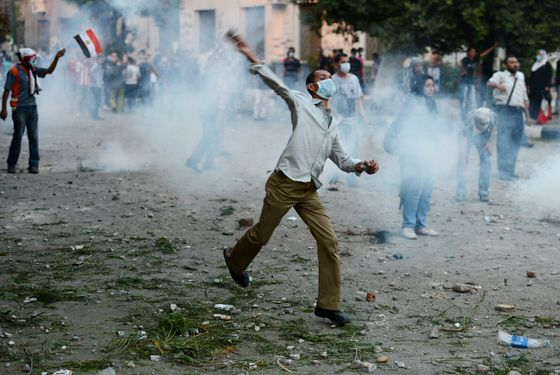 Egyptian protesters throw stones towards riot police during clashes near the US embassy in Cairo on September 13, 2012. Police used tear gas as they clashed with a crowd protesting outside the US embassy in Cairo against a film mocking Islam. AFP PHOTO/KHALED DESOUKI        (Photo credit should read KHALED DESOUKI/AFP/GettyImages)