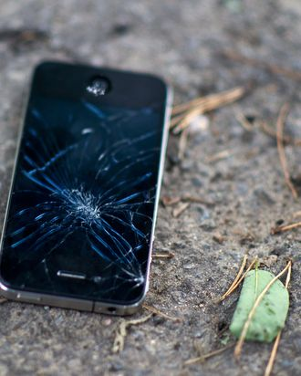 A broken and inoperable mobile phone lays on the ground