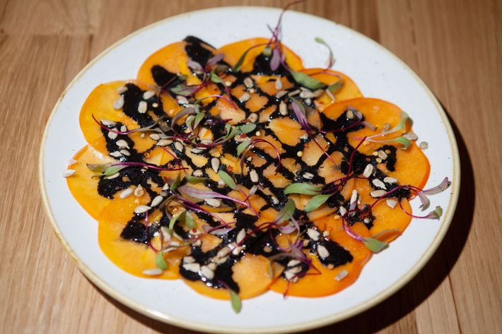 Persimmon carpaccio with squid ink and sunflower seeds.