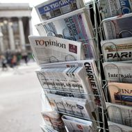 """A copy of the newspaper """"L'opinion"""" is pictured amongst other newspapers in a newsstand on May 15, 2013 in Paris. The newspaper, also available online, was released on May 15, 2013 in France."""