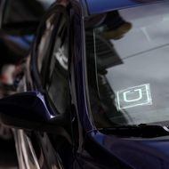 A sticker with the Uber logo is displayed in the window of a car on June 12, 2014 in San Francisco, California. The California Public Utilities Commission is cracking down on ride sharing companies like Lyft, Uber and Sidecar by issuing a warning that they could lose their ability to operate within the state if they are caught dropping off or picking up passengers at airports in California.